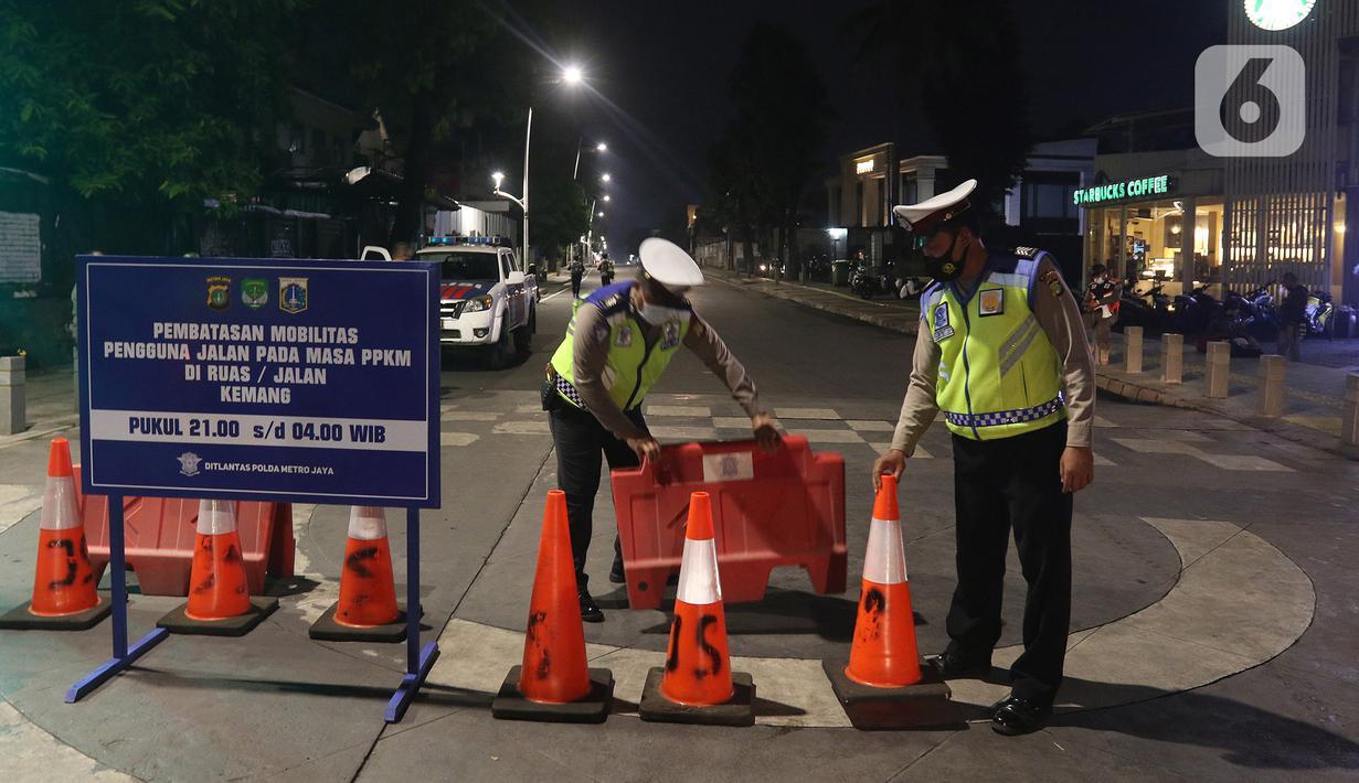 Polisi menyusun pembatas jalan di Jalan Kemang, Jakarta, Senin (21/6/2021). Penutupan jalan dalam rangka pembatasan mobilitas warga guna menekan penyebaran COVID-19 dilakukan mulai pukul 21.00 WIB hingga 04.00 WIB di 10 titik di Kota Jakarta. (Liputan6.com/Herman Zakharia)