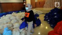 Seorang wanita membawa bansos berupa bahan pangan untuk didistribusikan kepada warga terpapar COVID-19 yang menjalani isolasi mandiri di rumah di Gedung Wanita, Kota Bogor, Jumat (9/7/2021). Bansos ini sumbangan instansi pemerintah dan swasta, pegawai negeri dan perorangan. (merdeka.com/Arie Basuki)