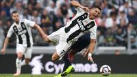 Bintang Juventus, Cristiano Ronaldo, terjatuh saat melawan Genoa pada laga Serie A Italia di Stadion Allianz, Turin, Sabtu (20/10). Kedua klub bermain imbang 1-1. (AFP/Marco Bertorello)