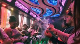 Wisatawan berbagi ganja dalam bus Green Line Trips di Los Angeles, Amerika Serikat, Sabtu (19/5). Tur bus Green Line Trips melakukan perjalanan dengan destinasi pemberhentian di toko-toko ganja lokal. (AP Photo/Richard Vogel)