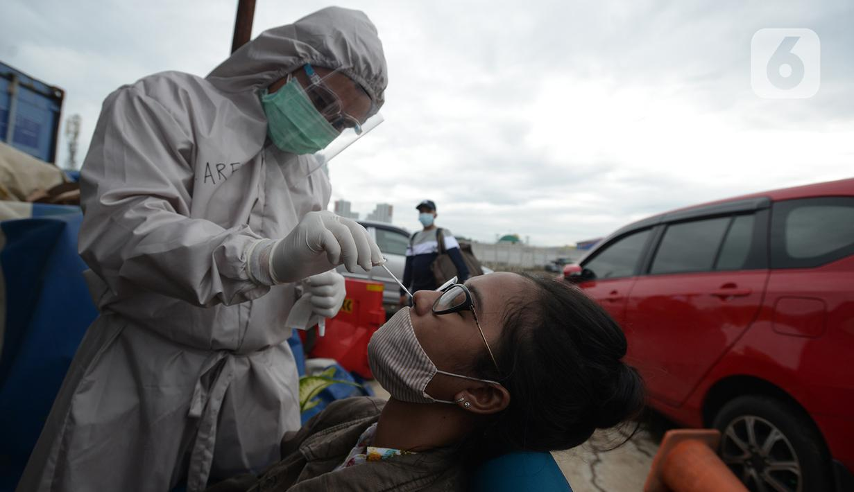 Petugas medis mengambil sampel lendir wisatawan untuk tes usap atau Swab Antigen di Pelabuhan Kali Adem, Jakarta, Kamis (31/12/2020). Pemeriksaan swab antigen wisatawan yang akan libur Tahun Baru di Kepulauan Seribu dilakukan untuk mencegah penyebaran COVID-19. (merdeka.com/Imam Buhori)