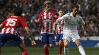 Bomber Real Madrid, Cristiano Ronaldo, berduel dengan striker Atletico Madrid, Antonie Griezmann, dalam laga yang berlangsung di Santiago Bernabeu, Minggu (8/4/2018). (AP Photo/Francisco Seco)