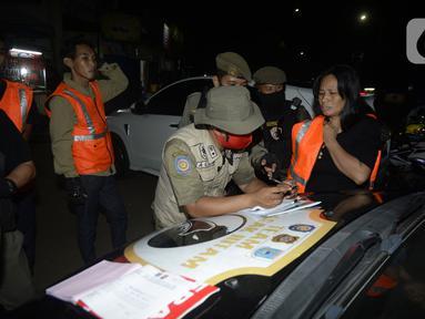 Petugas melakukan Operasi Yustisi mencegah penularan Covid-19 di Taman Perdamaian, Tangerang Selatan, Banten, Rabu (23/9/2020). Sebagai efek jera, warga yang tidak mengenakan masker diberi sanksi sosial berupa membersihkan toilet, menyapu, push up, dan denda Rp 50 ribu. (merdeka.com/Dwi Narwoko)