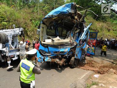 Bangkai bus maut Jakarta Wisata Transport berhasil diangkat dari jurang menggunakan derek di jalur alternatif Cikidang, Sukabumi, Jawa Barat, Minggu (9/9). Akibat kecelakaan bus masuk jurang tersebut, 21 orang dinyatakan tewas. (Merdeka.com/Arie Basuki)