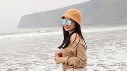 Tasya Rosmala berpose kece dengan setelan outfit dengan warna senada dan tambahan kaca mata saat berada di Pantai Grajakan,Banyuwangi. (Liputan6.com/IG/@tasya_ratu_gopo)
