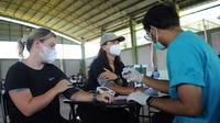 Dua warga negara asing (WNA) menjalani pemeriksaan tekanan darah sebelum menerima vaksin virus corona COVID-19 AstraZeneca di klinik vaksinasi massal darurat di Denpasar, Bali, Selasa (6/7/2021). Indonesia tengah memerangi gelombang infeksi baru yang belum pernah terjadi sebelumnya. (SONNY TUMBELAKA