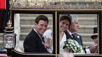 Putri Eugenie dan Jack Brooksbank menyapa mesyarakat saat menaiki kereta kencana usai melangsungkan pernikahan di Kapel St. George, Windsor Castle, London, Inggris,  Jumat (12/10). (Andrew Matthews, Pool via AP)