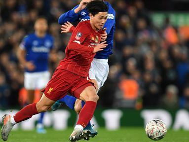 Gelandang Liverpool, Takumi Minamino menggiring bola dari kawalan pemain Everton, Gylfi Sigurdsson pada pertandingan babak ketiga Piala FA di Anfield, Minggu (5/1/2020). Pemain Jepang menjalani debut bersama Liverpool dengan menjadi starter dipertandingan tersebut. (AFP/Paul Ellis)