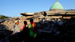 Warga melihat reruntuhan bangunan Masjid Jamiul Jamaah yang rusak akibat gempa bumi di Bangsal, Lombok Utara, Rabu (8/8). Berdasarkan kesaksian warga, diduga puluhan korban yang sedang melaksanakan pengajian tertimbun bangunan masjid. (AP/Tatan Syuflana)