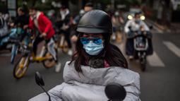 Seorang perempuan yang memakai masker untuk mengurangi risiko tertular virus corona COVID-19 bepergian dengan sepeda listrik selama jam sibuk di Beijing, China pada 14 Oktober 2020. (Photo by NICOLAS ASFOURI / AFP)