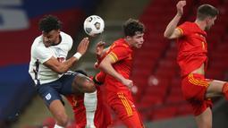 Bek Inggris, Tyrone Mings, berebut bola dengan bek Wales, Ben Cabango, pada laga persahabatan di Stadion Wembley, Jumat (9/10/2020) dini hari WIB. Inggris menang 3-0 atas Wales. (AFP/Nick Potts/pool)