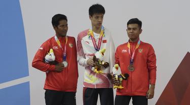 Perenang Indonesia, Guntur dan Zulkarnain Zaki, meraih medali pada Asian Para Games di Stadion Aquatik, Jakarta, Selasa (9/10/2018). Indonesia meraih medali perak dan perunggu di nomor 100 meter gaya dada putra kategori SB8. (Bola.com/M Iqbal Ichsan)