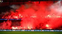 Pendukung Paris Saint-Germain menyalakan suar saat PSG melawan Real Madrid di pertandingan Liga Champions leg kedua di stadion Parc des Princes di Paris (6/3). Mereka juga menyanyikan lagu bernada cemoohan kepada Real Madrid. (AP Photo / Francois Mori)
