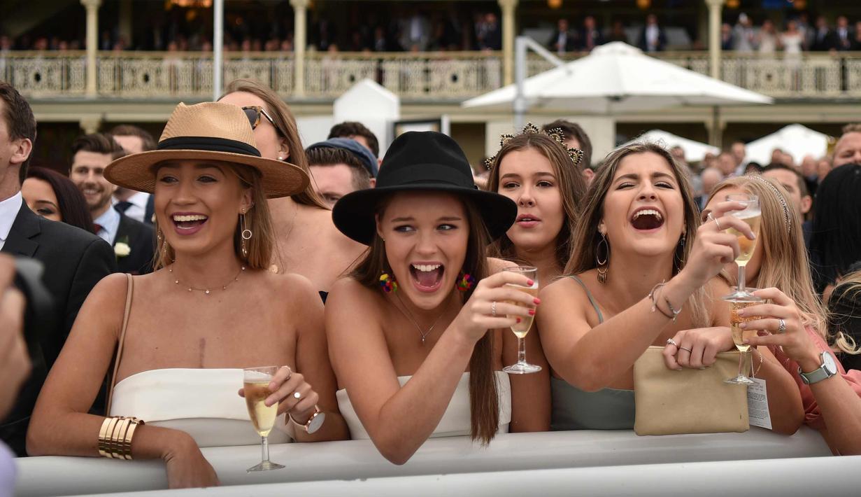 Sejumlah wanita bersorak saat menyaksikan pacuan kuda Everest 2017 di Royal Randwick di Sydney, Australia (14/10). Para wanita ini tampil cantik dengan busana yang dikenakannya . (AFP Photo/Peter Parks)