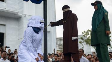 Petugas syariah mencambuk pekerja seks komersial (PSK) online di halaman Masjid Jamik Lueng Bata, Banda Aceh, Aceh, Jumat (20/4). Petugas syariah melakukan hukum cambuk terhadap dua PSK online. (CHAIDEER MAHYUDDIN / AFP)