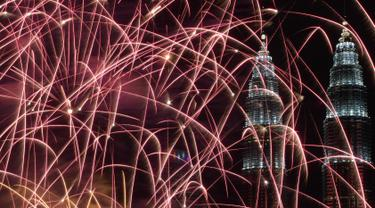Kembang api menghiasi langit di dekat Menara Kembar Petronas Malaysia saat malam pergantian tahun di Kuala Lumpur, Malaysia. (01/1/2018). Menara Kembar Petronas menjadi salah satu spot para wisatawan menikmati malam tahun baru. (AFP Photo / Mohd Rasfan)