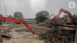 Petugas dibantu alat berat membersihkan sampah kayu dan bambu yang tersangkut di Pintu Air Manggarai, Jakarta, Rabu (9/10/2019). Sampah tersebut merupakan kiriman dari Bogor usai diguyur hujan deras tadi malam. (Liputan6.com/Faizal Fanani)