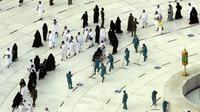 Pekerja melakukan disinfeksi untuk membantu mengekang penyebaran virus corona COVID-19 saat jemaah umrah tawaf mengelilingi Ka'bah pada awal bulan suci Ramadhan di Masjidil Haram, Mekkah, Arab Saudi, Senin (12/4/2021). (AP Photo/Amr Nabil)