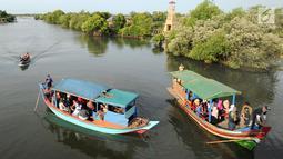 Perahu wisata melintasi kerumunan wisatawan yang berjalan di atas Jembatan Cinta di Wisata Mangrove, Tarumajaya, Bekasi, Minggu (30/12). Wisata tersebut awalnya merupakan Pusat Restorasi dan Pembelajaran Mangrove (PRPM) Bekasi. (merdeka.com/Arie Basuki)
