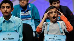 Sohum Sukhatankar (11), peserta dari Texas, bereaksi saat mendengarkan peserta lain mengeja dalam bahasa Inggris pada acara 90th Scripps National Spelling Bee di Oxon Hill, Maryland, Kamis (1/6). (AP Photo/Jacquelyn Martin)