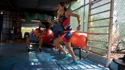 Atlet triathlon Kuba, Leslie Amat berlari dengan tali di pinggangnya di bawah pengawasan sang pelatih, Dioseles Fernandez di teras rumahnya di Havana, Senin (20/4/2020). Atlet Kuba tak bisa berlatih di fasilitas olahraga seperti biasanya selama pademi corona. (AP /Ismael Francisco)