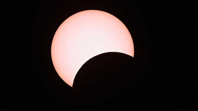 Bulan menutupi sebagian matahari selama gerhana matahari cincin (Annular Solar Eclipse) yang terlihat dari Mandalay di Myanmar, Minggu (21/6/2020). Sebagian penduduk Bumi bisa menyaksikan fenomena langka, Gerhana Matahari Cincin. (Ye Aung THU / AFP)