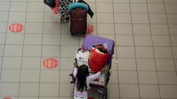 Penumpang terlihat di Bandara Internasional Arturo Merino Benitez di Santiago setelah Chile menutup perbatasannya, Senin (5/4/2021). Kasus COVID-19 melonjak di Chile meskipun negara tersebut diketahui sebagai salah satu negara dengan proses vaksinasi tercepat di dunia. (MARTIN BERNETTI/AFP)