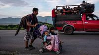 Seorang imigran Honduras mendorong kereta bayi dengan dua anaknya dalam perjalanannya menuju AS di Oaxaca, Meksiko, 29 Oktober 2018. Kereta dorong bayi tak hanya untuk balita mereka, tetapi juga dapat digunakan membawa barang-barang. (Guillermo Arias/AFP)