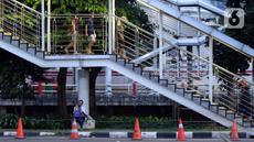 Warga bersandar di salah satu tiang JPO di kawasan Jalan HR Rasuna Said, Jakarta, Rabu (8/7/2020). Wabah Covid-19 memengaruhi kondisi kesejahteraan masyarakat dan pertumbuhan ekonomi Indonesia pada tahun 2020 yang diproyeksikan -0,4 sampai dengan 1,0 persen. (Liputan6.com/Helmi Fithriansyah)