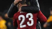 Manajer Liverpool Jurgen Klopp memeluk gelandang Liverpool, Xherdan Shaqiri pada laga putaran ketiga Piala FA melawan Wolverhampton Wanderers di Molineux Stadium, Senin (7/1). Liverpool tersingkir dari Piala FA setelah takluk 1-2. (Paul ELLIS/AFP)