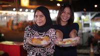 Meitry Nur Fazrina (kiri) dan Qorry Natawijaya (kanan) adalah mantan pramugari yang kini berjualan lontong sayur di jalan. Bisnis keduanya laris-manis, dan kini mereka bisa bertahan dari penghasilan lontong sayurnya. (Foto: Liputan6.com).