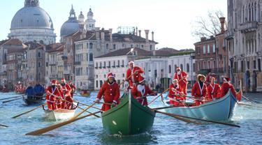 Ratusan orang mengenakan kostum Santa Claus mendayung perahu berparade di sepanjang Canal Grande di Venesia, Italia, (17/12). Sekitar dua ratus pendayung memberikan kehidupan pada prosesi air tradisional Santa Claus. (Andrea Merola / ANSA via AP)