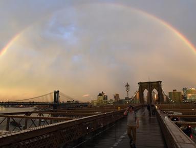 Pejalan kaki melintasi Jembatan Brooklyn saat pelangi menghiasi langit New York City, AS (15/5). Jembatan Brooklyn adalah salah satu jembatan suspensi tertua di Amerika Serikat. (AFP Photo/Hector Retamal)