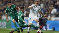 Pemain Real Madrid, Marcos Llorente (kanan) mengecoh dua pemain Leganes pada perempat final Copa del Rey di Santiago Bernabeu stadium, Madrid, (24/1/2018). Leganes menang 2-1. (AP/Francisco Seco)