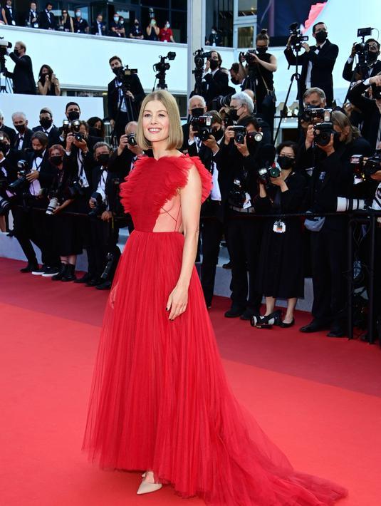 Rosamund Pike tampil di red carpet Cannes Film Festival 2021 dalam balutan gaun tulle merah dari Dior. Gaun ini didesain sendiri oleh Maria Grazia Chiuri. Foto: Document/Dior.