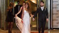 Bintang sepak bola, Lionel Messi berjalan di karpet merah bersama istrinya Antonella Roccuzzo di Rosario, provinsi Santa Fe, Argentina (30/6). Acara ini dihadiri banyak pesepakbola dan selebriti termasuk penyanyi pop Shakira. (AFP Photo/Eitan Abramovich)