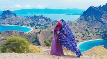 Perempuan yang memiliki channel youtube dengan subscriber 16,8 juta sampai sekarang ini tampak bahagia saat liburan di Labuan Bajo. Menggunakan pakaian serba ungu dan merah, ia memegang kain khas nusantara dengan lepas. (Liputan6.com/IG/@riaricis1795)