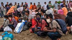 Pengungsi etnis Rohingya beristirahat setelah tiba di pesisir pantai Lancok, di Kabupaten Aceh Utara, Kamis (25/6/2020). Nelayan Indonesia menemukan hampir 100 orang etnis Rohingya, termasuk 30 orang anak-anak terdampar di tengah laut dengan kondisi kapal rusak. (AP Photo/Zik Maulana)