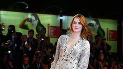 """Aktris Emma Stone berjalan di karpet merah saat tiba menghadiri pemutaran film """"The Favorite"""" selama Festival Film Venice ke-75 di Venice Lido, Italia, (30/8). Emma Stone tampil cantik dengan gaun transparan warna krem. (AFP Photo/Vincenzo Pinto)"""