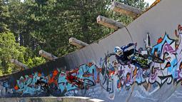 Freestyler sepeda saat asyik memacu sepedanya di jalur luge di Bosnia-Herzegovina , Jumat (8/8/2015). Kawasan ini tidak dirawat dan dibiarkan runtuh akibat digunakan markas tentara Bosnia dan Herzegovina pada perang 1991. (Reuters/Dado Ruvic)
