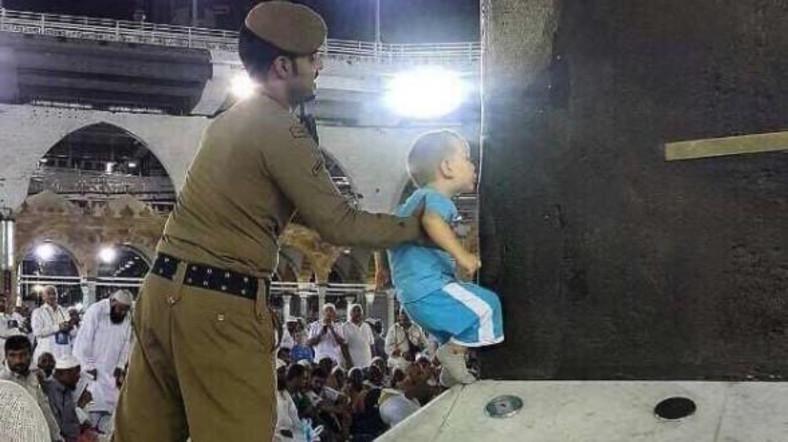 Foto petugas membantu bocah mencium Kakbah yang menuai pujian netizen. (Twitter)
