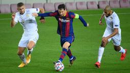 Penyerang Barcelona, Lionel Messi, berebut bola dengan gelandang Ferencvaros, Eldar Civic, pada matchday 1 Grup G Liga Champions 2020/2021 di Camp Nou, Rabu (21/10/2020) dini hari WIB. Barcelona menang 5-1 atas Ferencvaros. (AFP/Lluis Gene)