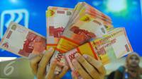 Petugas Bank menunjukkan uang pecahan rupiah di Bank BRI Syariah, Jakarta, Selasa (28/2). Pelemahan rupiah ini seiring dengan mata uang lainnya di Asia. (Liputan6.com/Angga Yuniar)