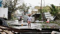 Warga berjalan di samping bangunan yang roboh akibat Topan Mangkhut di kota Tuguegarao di provinsi Cagayan, timur laut Filipina (15/9). Aktivitas sekolah dihentikan sementara dan kantor pemerintahan telah ditutup. (AP Photo/Aaron Favila)
