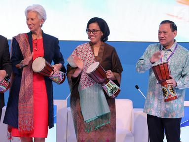 Menko Kemaritiman Luhut Pandjaitan, Direktur Pelaksana IMF Christine Lagarde, Menkeu Sri Mulyani bersama Gubernur BI Agus Martowardojo memukul tifa saat pembukaan High - Level International Conference di Jakarta, Selasa (27/2). (Liputan6.com/JohanTallo)