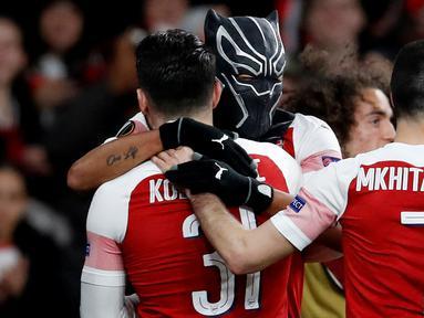 Striker Arsenal Pierre-Emerick Aubameyang mengenakan topeng superhero Black Panther memeluk rekannya usai mencetak gol ke gawang Stade Rennes pada leg kedua babak 16 besar Liga Europa di Stadion Emirates, London, Inggris  (14/3). (REUTERS/David Klein)