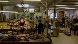Seorang pemahat mengerjakan patung Yesus dari kayu di bengkel Arte Martinez, Horche, Spanyol, Senin (29/3/2021). Untuk dua tahun berturut-turut, Spanyol harus membatalkan prosesi Minggu Paskah untuk membantu menghentikan penyebaran COVID-19. (AP Photo/Bernat Armangue)