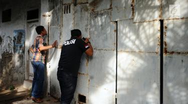 Petugas melakukan pengintaian rumah terduga penampung TKI Ilegal di Jalan Percetakan Negara X, Jakarta, Rabu (31/5). Dengan membawa satu tersangka, petugas Dirtipidum Mabes Polri melakukan pencarian barang bukti baru. (Liputan6.com/Helmi Fithriansyah)