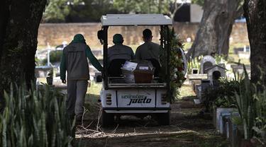 Petugas mengangkut peti jenazah Jose Valdelirio yang diyakini meninggal akibat virus corona di pemakaman Campo da Esperanca di Taguatinga, Brasilia, Brasil, Rabu (3/3/2021). Brasil pada Selasa (2/3) mencatat rekor tertinggi dengan 1.641 kematian akibat Covid-19 dalam 24 jam. (AP Photo/Eraldo Peres)