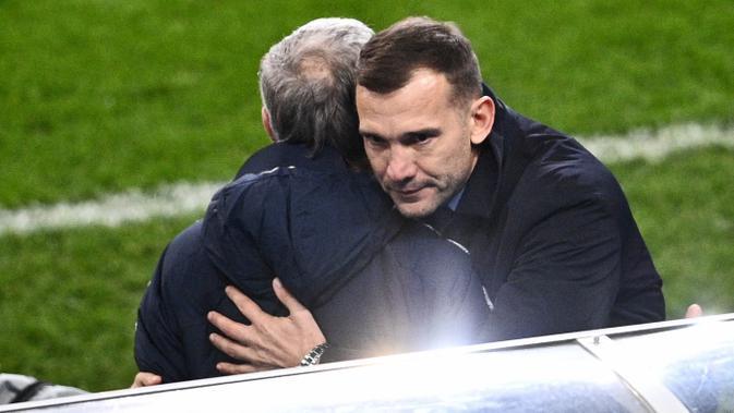 Pelatih Ukraina, Andriy Shevchenko, memeluk pelatih Prancis, Didier Deschamps, pada laga Kualifikasi Piala Dunia di Stadion Saint Denis, Paris, Kamis (25/3/2021). Kedua tim bermain imbang 1-1. (AFP/Anne-Christine Poujoulat)